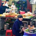a girl sitting in front a market stall eating a meal on a low set table