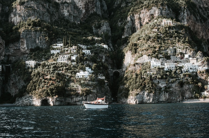 Cliffside buildings and a boat in the sea in Praiano, Italy