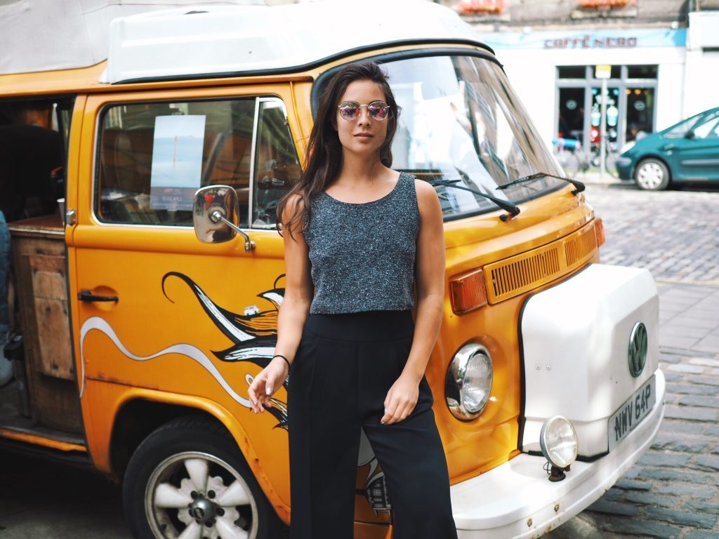 a woman with sunglasses stands in front of a yellow van with graffiti on it