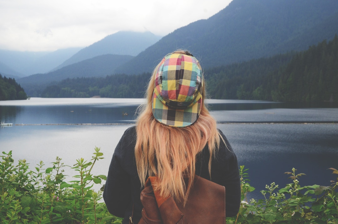 A woman in a colourful hat stands facing a lake in British Columbia