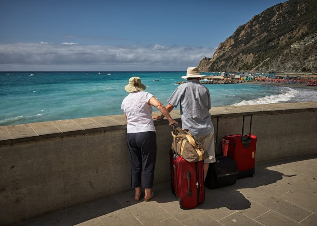 a man and woman stand looking over a bay with two red suitcases