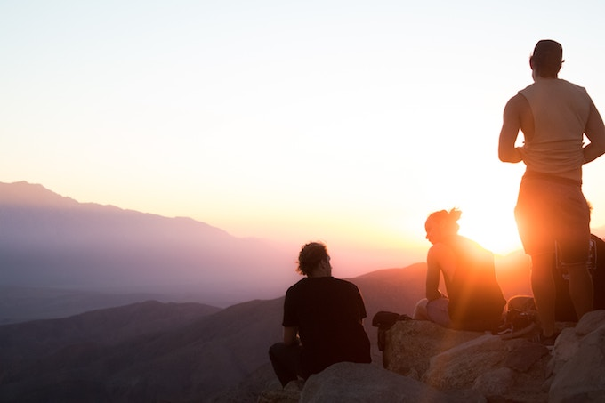 Three people on a cliff in Joshua Tree, California