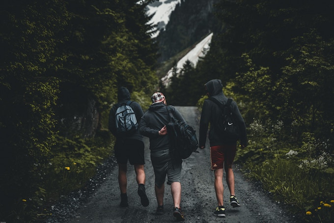 Three friends in shorts and hoodies walking outdoors