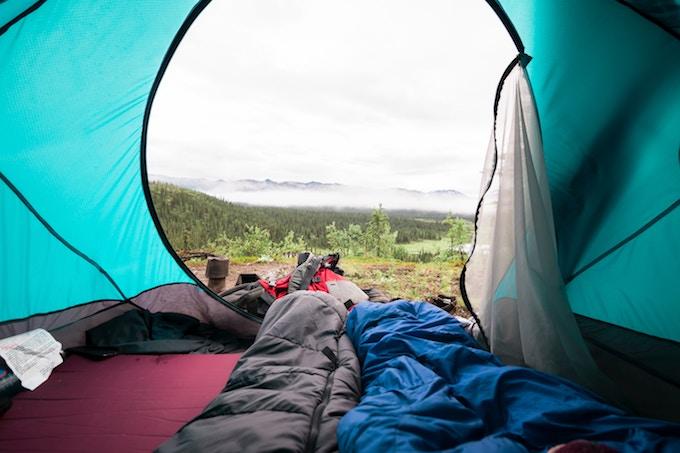 Sleeping bags inside a tent overlooking the woods in Alaska