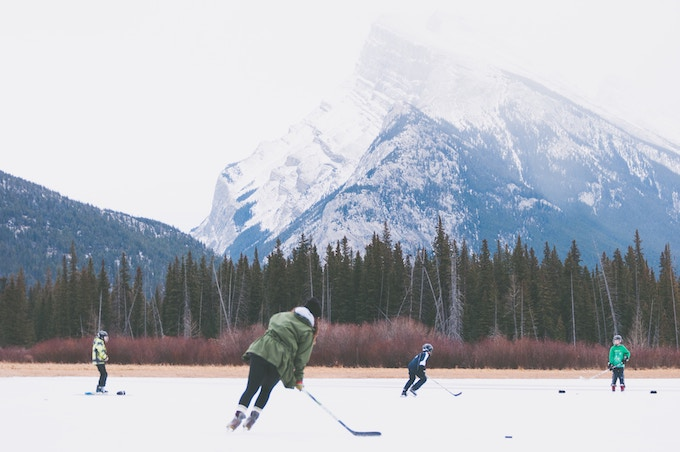 People playing hockey on a frozen lake at the base of a mountain