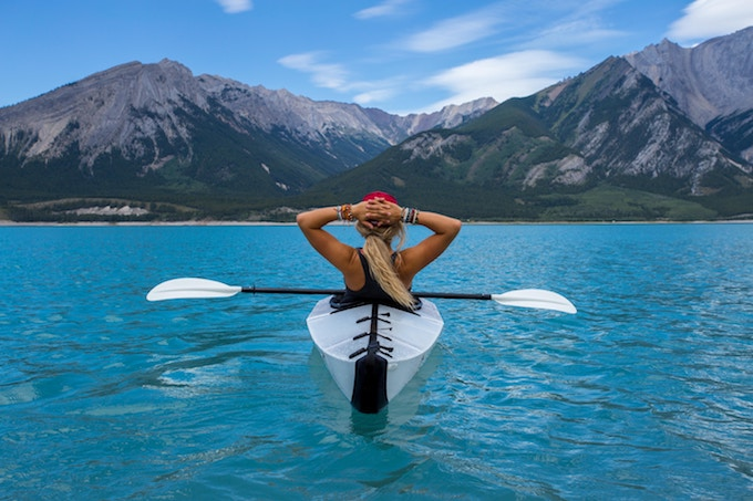 a woman reclining in a kayak on a lake in Canada