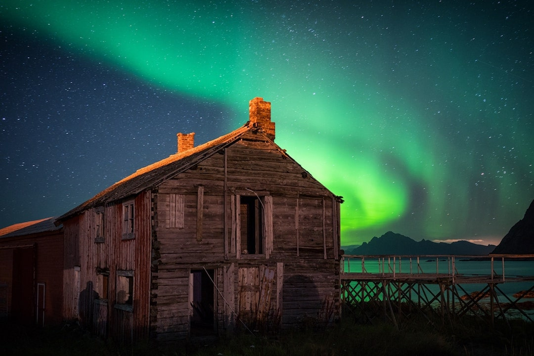 The northern lights over an abandoned barn in Hovden, Norway