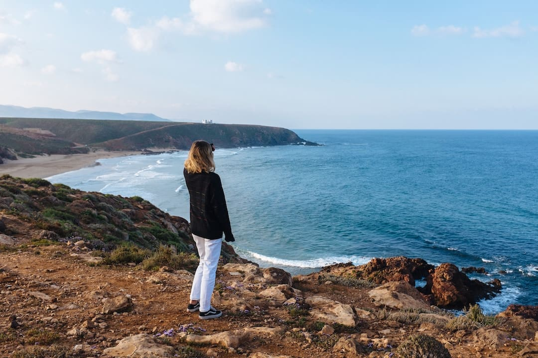 A woman standing looking out onto the ocean in Morocco