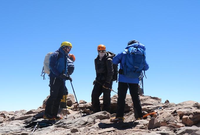 A group of three people climbing Mount Kilimanjaro