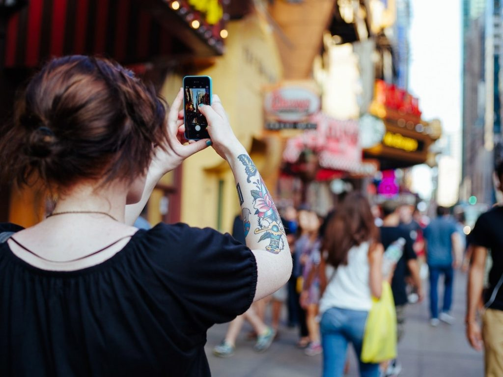 Woman taking a photo with iPhone in Times Square, New York