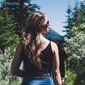 woman wearing black spaghetti strap crop top standing in front of trees while looking left side during daytime