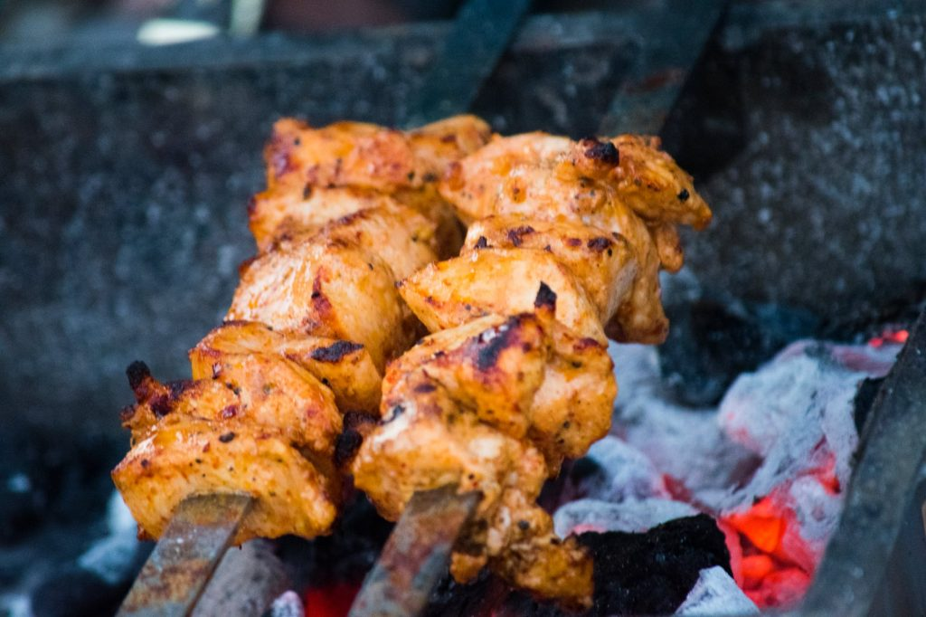 marinated chicken being cooked over hot coals