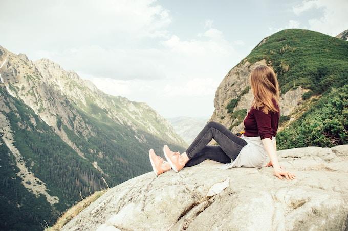 a woman sitting on a mountain