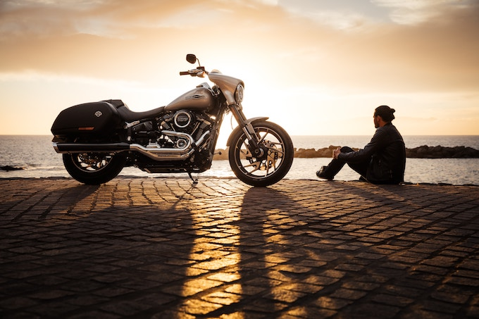 A man sitting beside a motorcycle at sunset