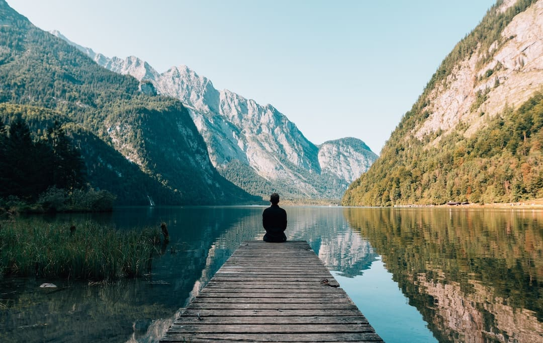 A man sitting on the edge of a dock facing a mountain in Germany