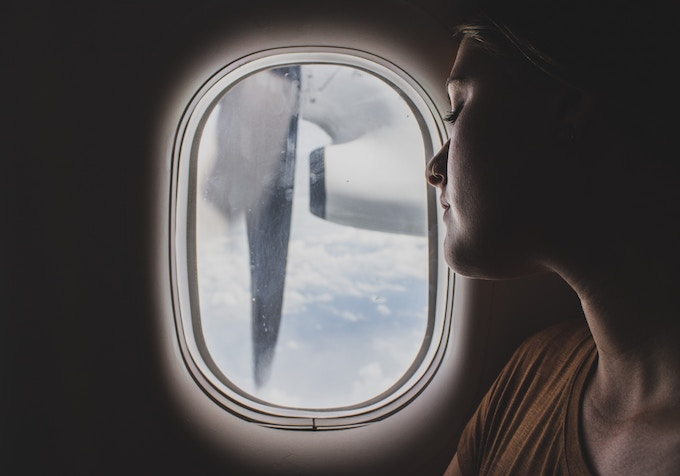 A woman sleeping against the window of a plane