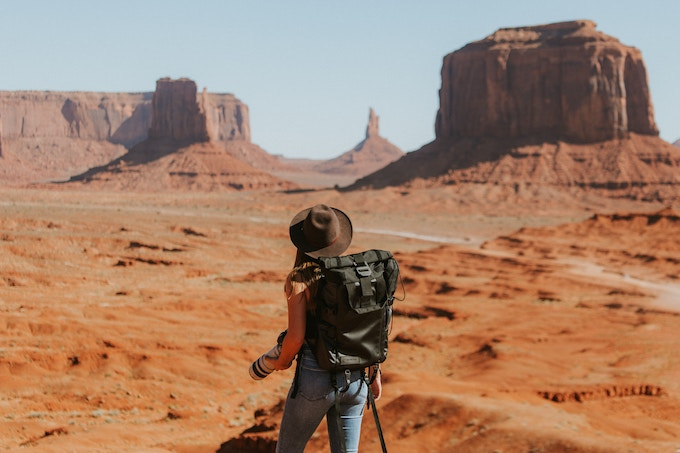 A woman in a hat and a green backpack standing with her back to the camera in Oljato-Monument Valley, USA