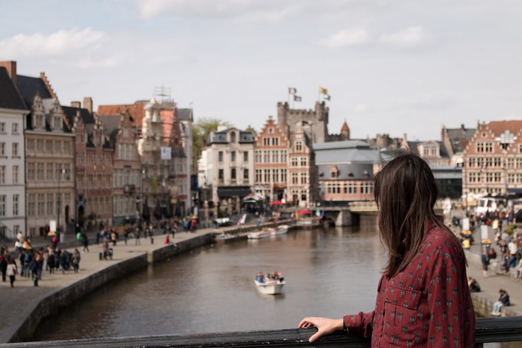 woman standing on a bridge looking back across a city