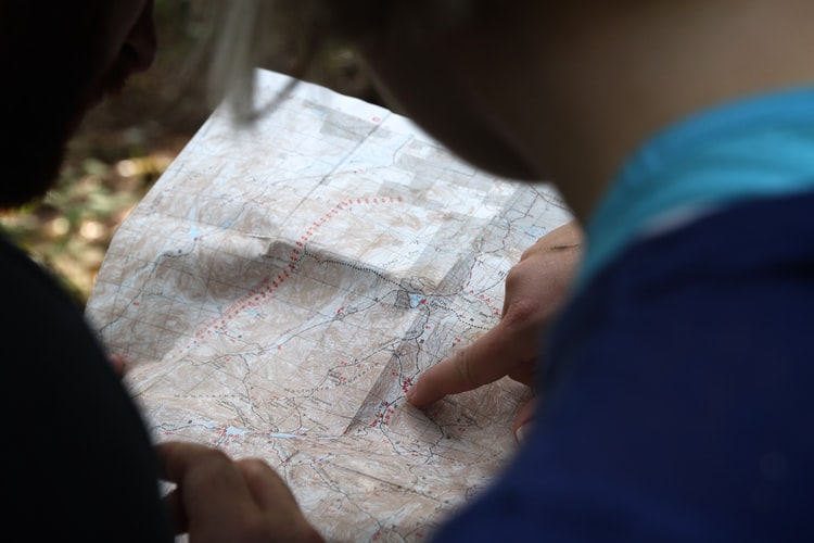 two people at a map and pointing at something on it