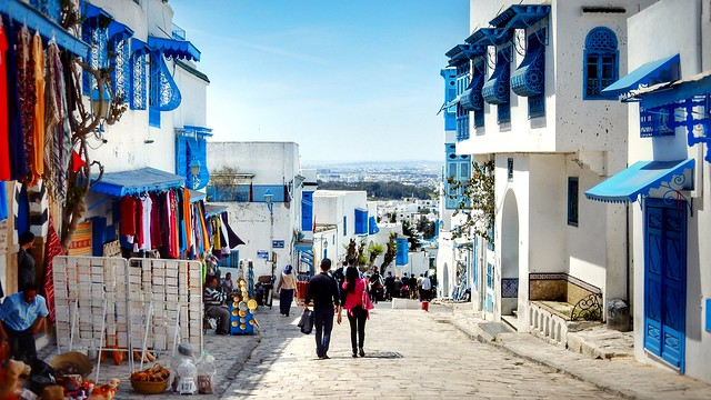 two people walking along a road with blue and white buildings