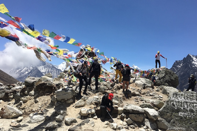 a group of people standing at a view point in the himalayas with colourful flags
