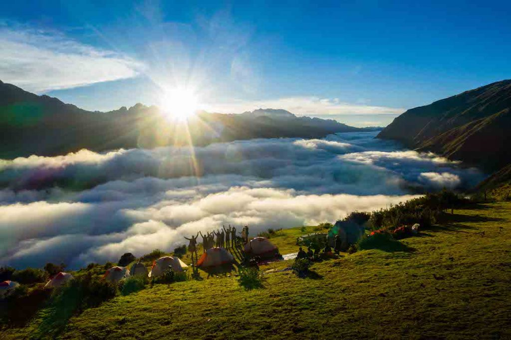 a long distance shot a people on the mountains with tents looking out at the clouds
