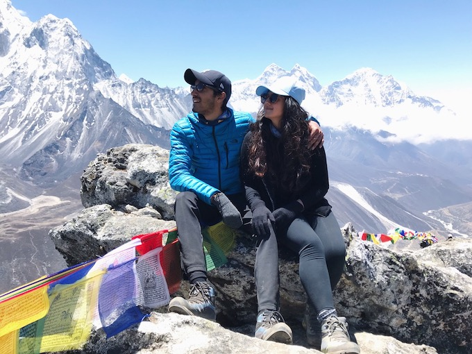 a couple sitting on a rock with the himalayas in the background
