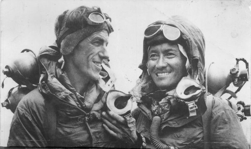 black and white picture of two smiling climbers in their summit gear