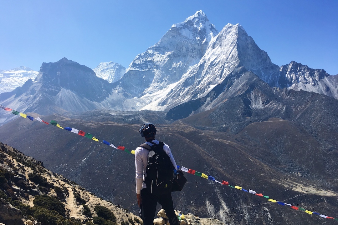 climber with a backpack stands in front of mountain peaks with colourful flags