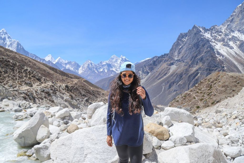 a girl in a blue cap in a mountain valley smiling