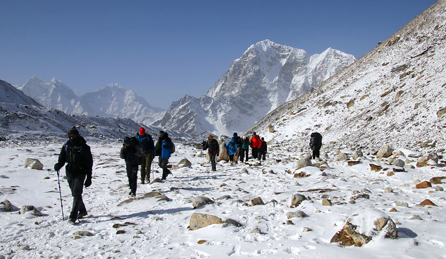 A tour group makes its way through icy alpine plateaus