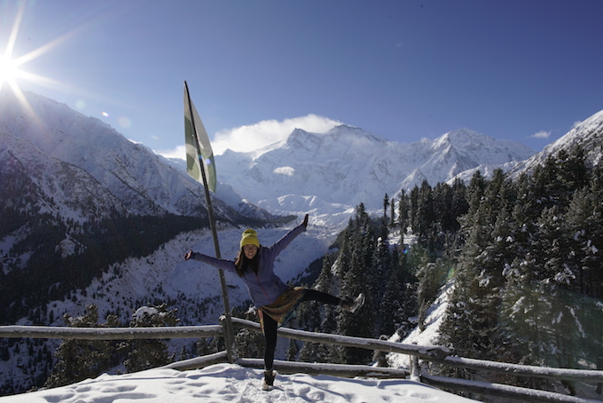 a girl holding a yoga pose on with a backdrop of snowcapped mountains