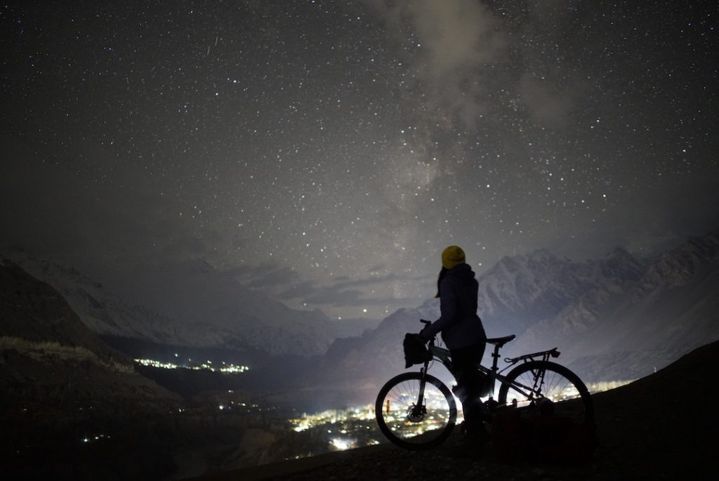 silhouette of a girl with a cycle against a night sky with stars