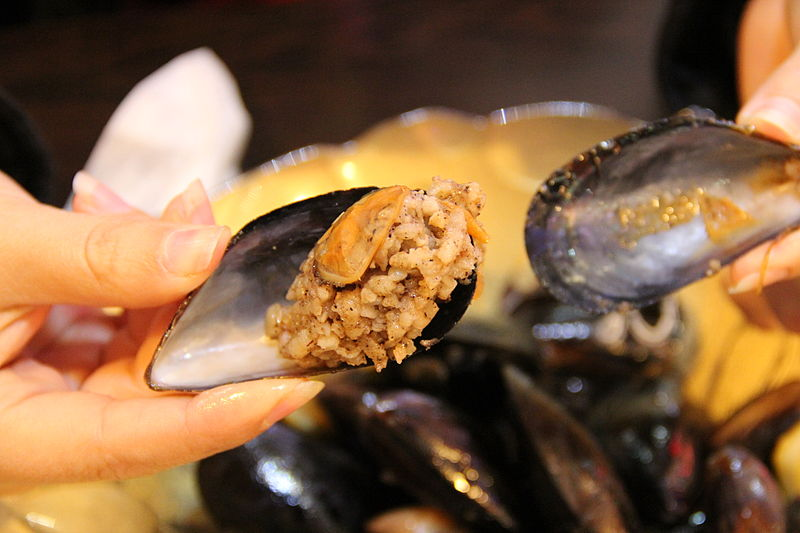 Person holding midye dolma, stuffed mussels, in Istanbul, Turkey