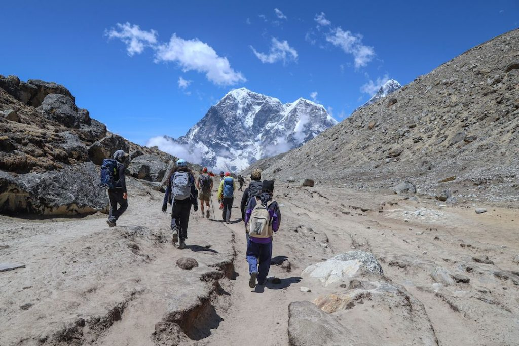 a group of people walking through the mountains