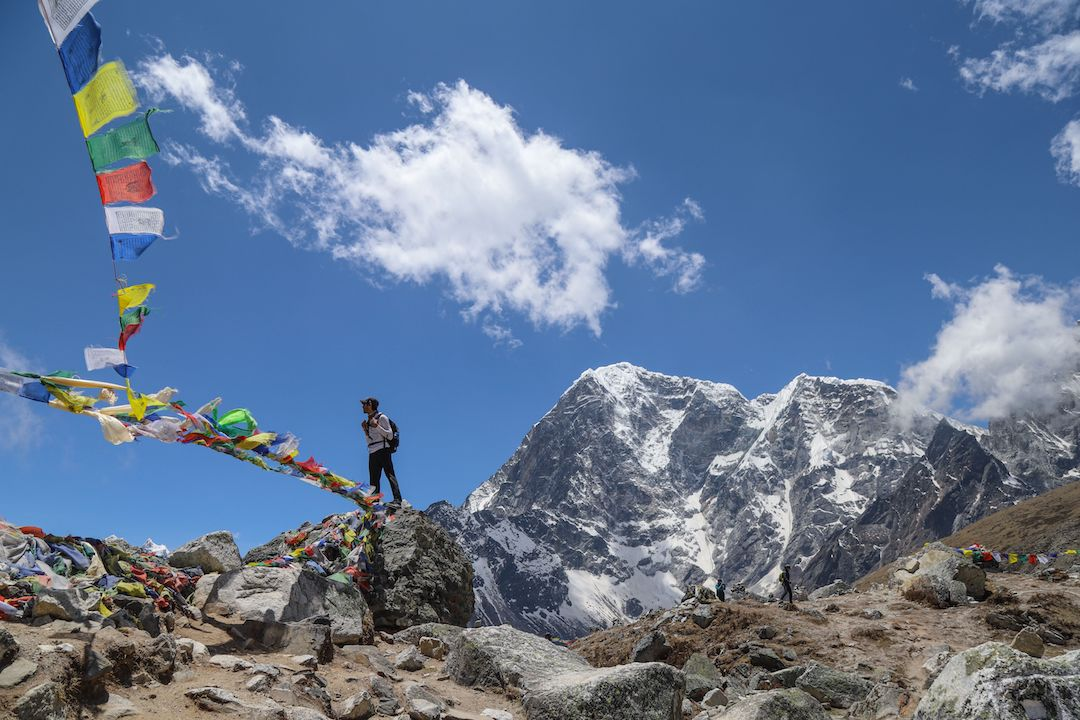 a man standing in a mountain range with colourful flags fluttering in the air