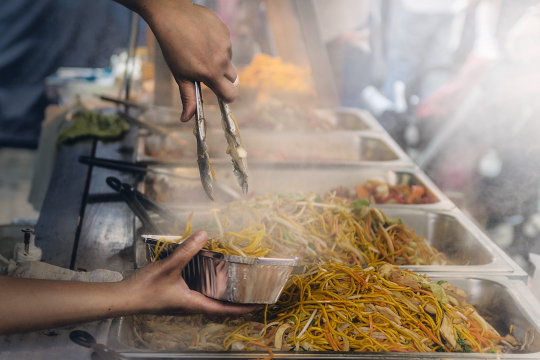 steam coming off piles of noodles as a street vendor serves them up