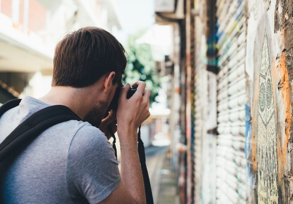 Man holding camera and taking photos on the street