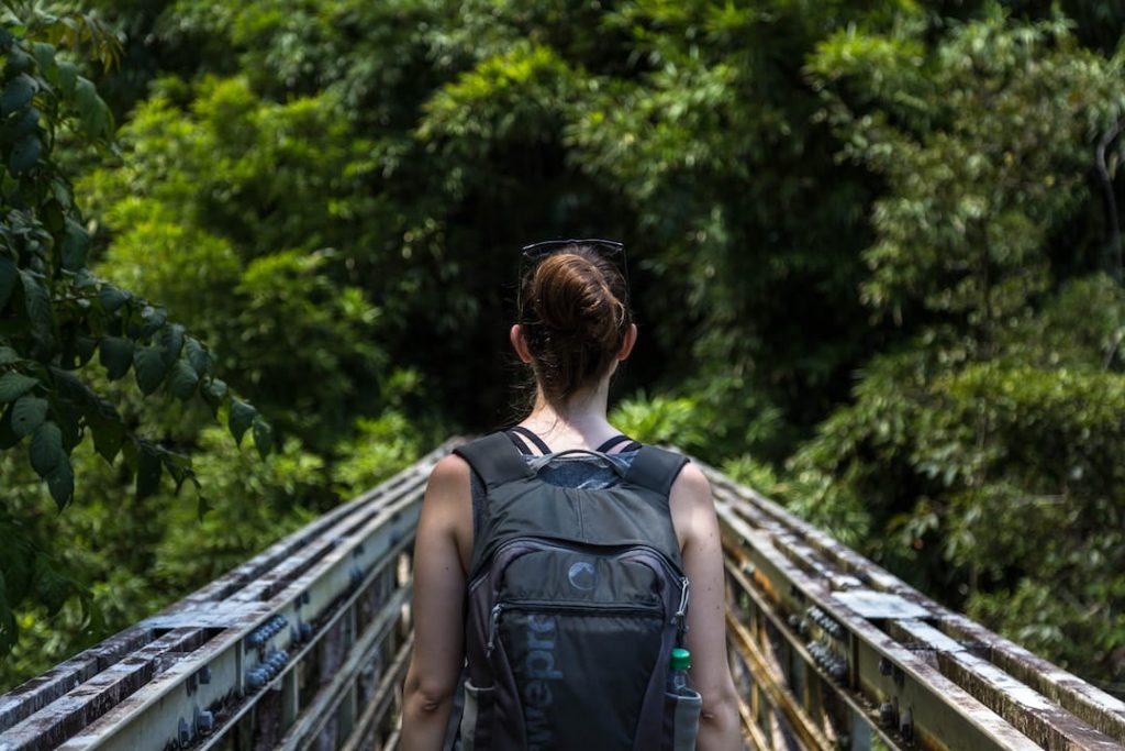 Woman walking across a bridge wearing a backpack