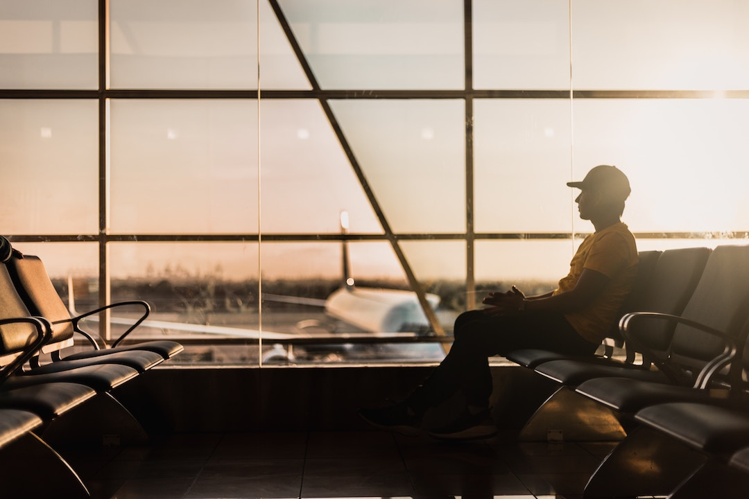 man sitting an an airport against glass panelled window with planes in the background
