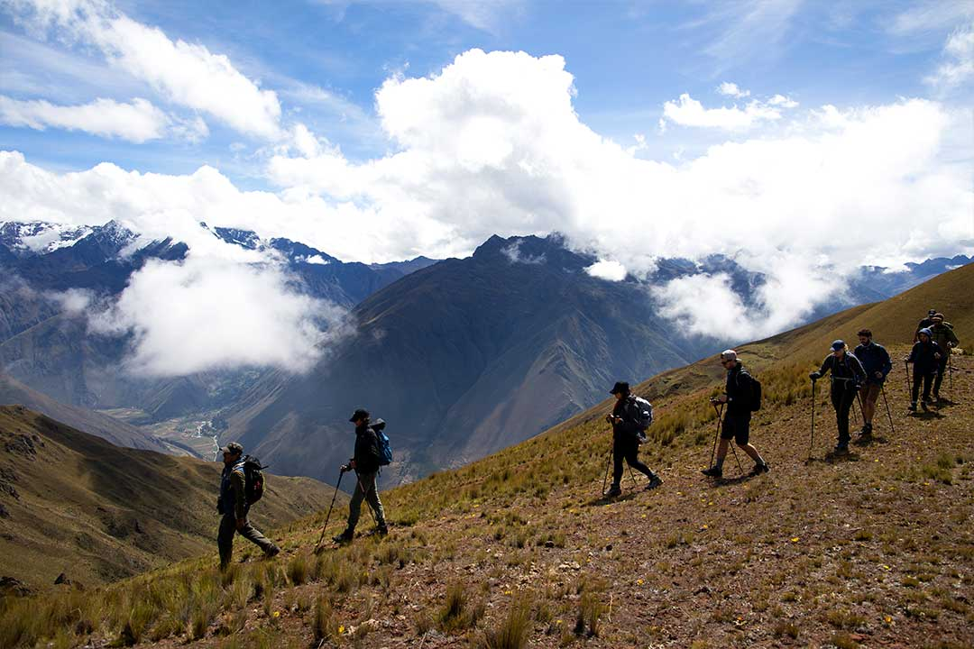 a group of trekkers walking along a ridge in the andes