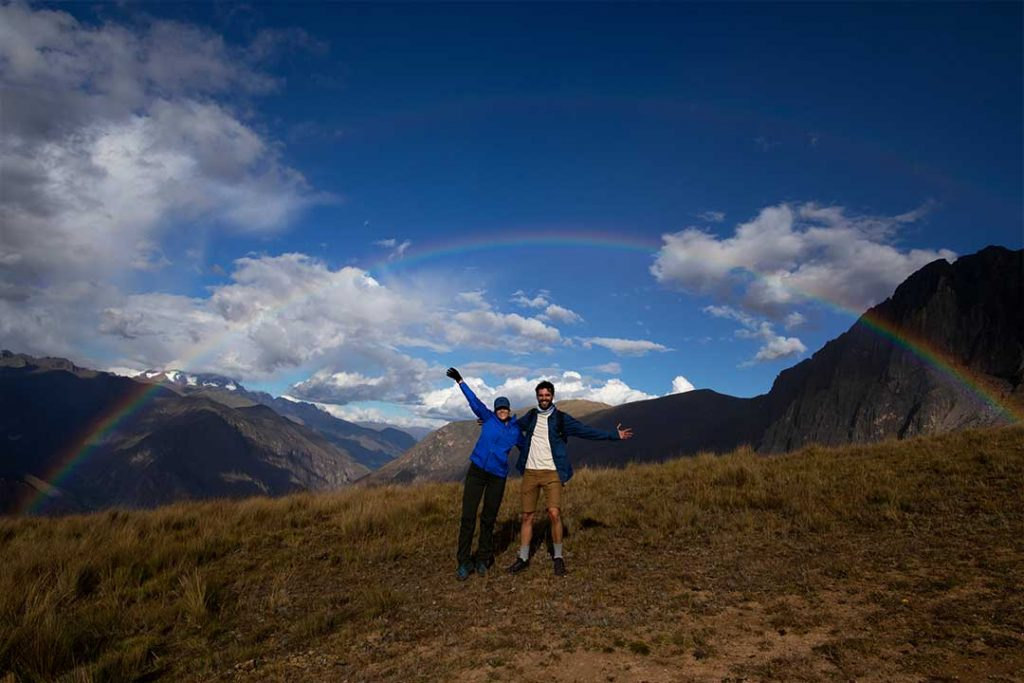 two people in the mountain waving at the camera