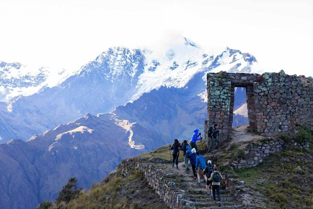 a group of trekkers walking up to a stone doorway structure in the mountains