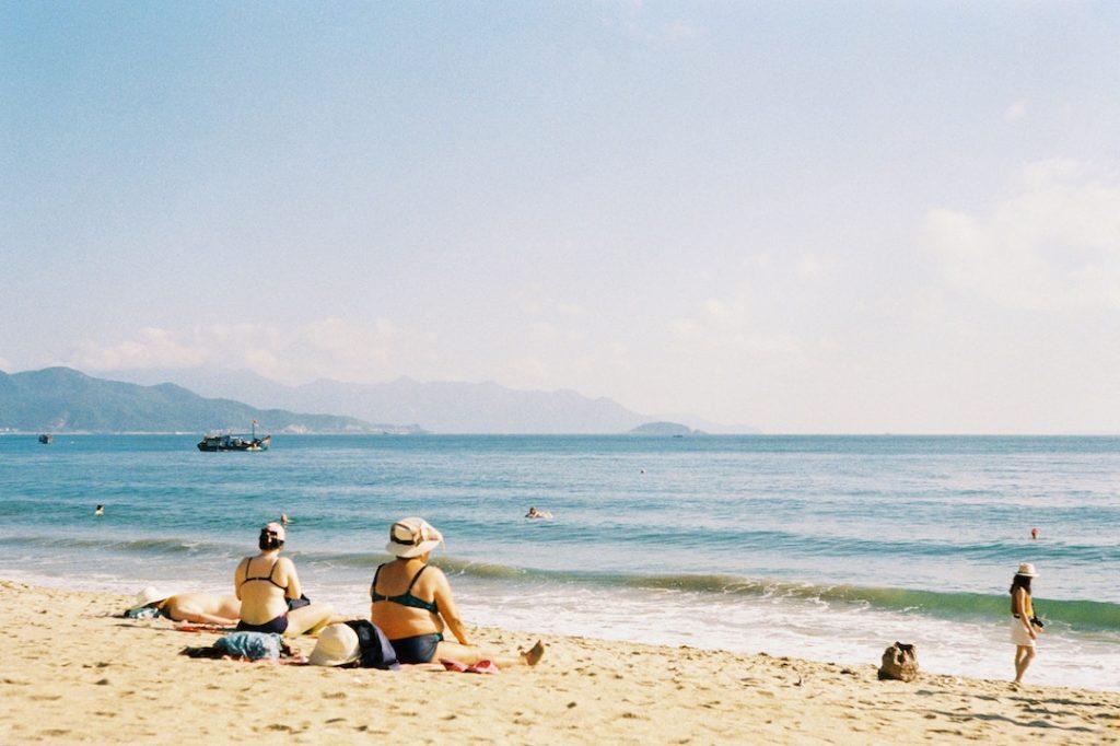 People sitting on a beach facing the ocean in Nha Trang, Vietnam