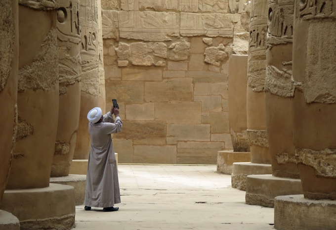 A man taking a photo of a temple in Luxor, Egypt