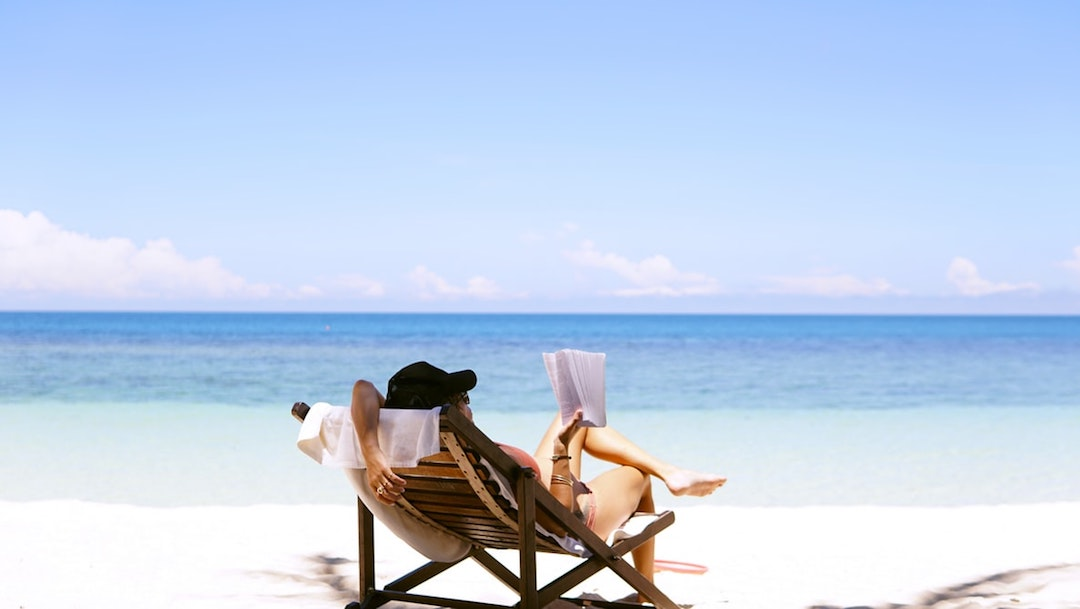 woman sits on brown wooden beach chair in front of the sea