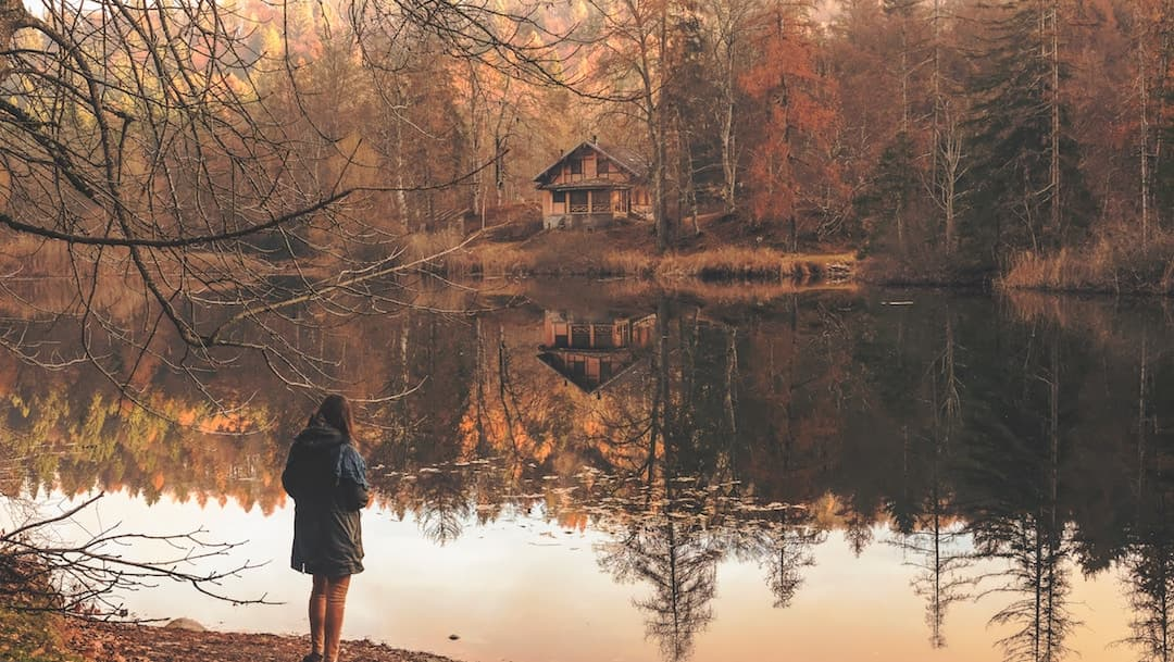 A woman standing in front of a lake in the Falll