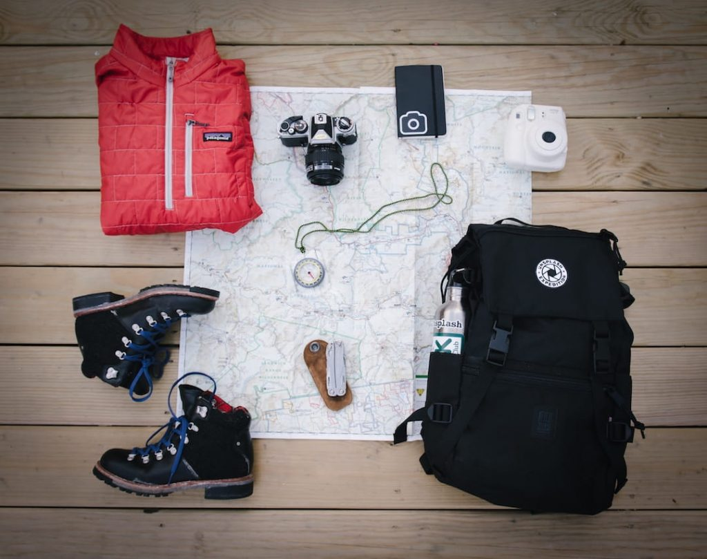 A map and hiking essentials arranged on the floor with a backpack