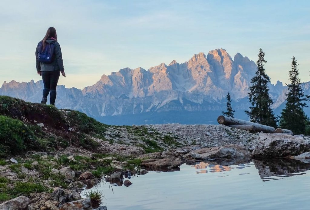 A woman standing beside a body of water and trees with mountains in the distance in Italy