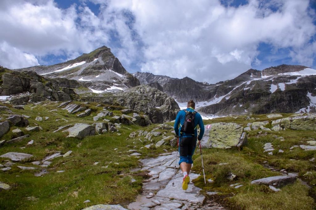 Man hiking with trekking poles along a path with mountains in the background